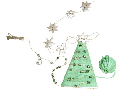 Handmade christmas tree isolated on white background. Decoration made from thread and decorated with beads. Stock Photo