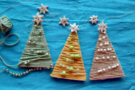 Handmade christmas trees on blue creped paper. Decoration made from thread and decorated with beads. Stock Photo