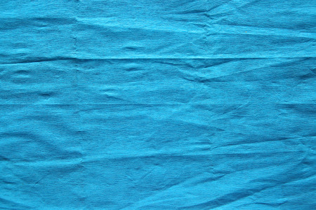 Blue creped paper background. Wrinkled crepe paper texture.