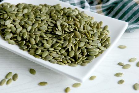 Raw pumpkin seeds. Green unshelled pumpkin seed in plate.