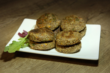 Buckwheat burgers in plate. Buckwheat burgers with carrots and parsley, vegan dish. Stock Photo