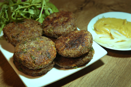 Buckwheat burgers in plate. Vegan cutlets made from buckwheat, carrots, parsley with mustard sausage. Stock Photo
