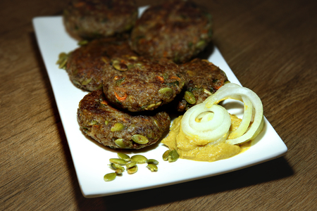 Buckwheat and pumpkin seed burgers in plate. Vegan cutlets made from buckwheat, pumpkin seeds, carrots, parsley with mustard sausage. Stock Photo