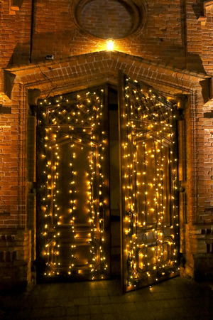 Ancient opened door with decorative light garlands. Outdoor light decoration in christmas time. Stock Photo