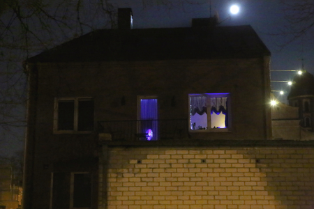 Old house in night city. Blue light from the windows of the house in the dark street.