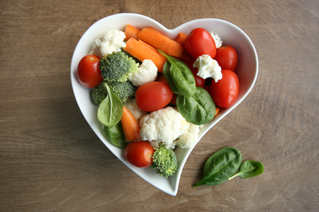 Heart shaped plate with assorted fresh vegetables, top view. Raw vegetables (tomatoes, cauliflowers, broccoli, carrots, spinach) ingredients for snack, salad or soup. Stock Photo