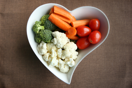 Heart shaped plate with assorted fresh vegetables, top view. Raw vegetables (tomatoes, cauliflowers, broccoli, carrots,) ingredients for snack, salad or soup.