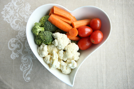 Heart shaped plate with assorted fresh vegetables, top view. Raw vegetables (tomatoes, cauliflowers, broccoli, carrots) ingredients for snack, salad or soup.