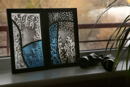 Stained glass with frosty drawing on windowsill. Handmade stained glass graphic pictures. Stock Photo
