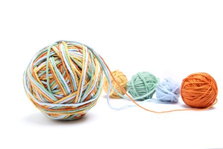 4 개의 색상 스레드에서 다채로운 큰 스레드 공입니다. 코 튼 스레드 공 흰색 배경에 고립입니다. 다른 색상 (오렌지, 노란색, 녹색, 파란색) 스