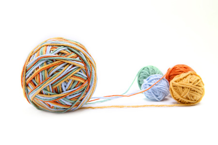 Colorful big thread ball from four color thread. Cotton thread balls isolated on white background. Different color (orange, yellow, green, blue) thread mix.