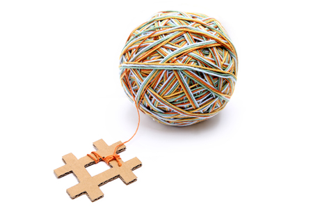 Hashtag made from cardboard with big colorful thread ball isolated on white background. Cotton thread ball made from different color (orange, yellow, green, blue) with hashtag sign  concept.