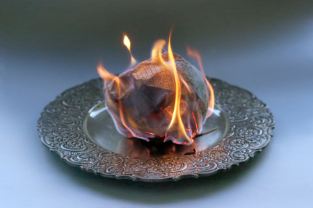 Document burning in vintage plate. Paper sheet with text burning in fire. Stock Photo