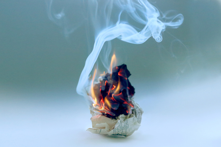 Crumpled paper burning in fire .  Burning old scheme document with flame and smoke.
