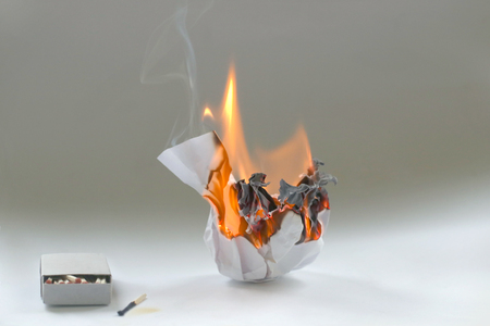 Crumpled paper burning in fire and matchbox . Burning white paper ball in flame and box of matches.
