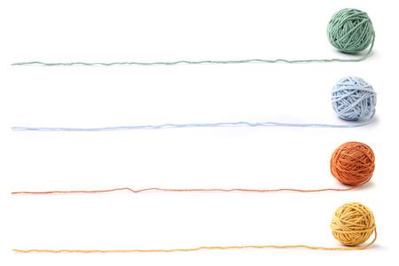 Bunte Baumwollthreadbälle lokalisiert auf weißem Hintergrund. Satz von vier Farbkugeln (orange, gelb, grün, blau).