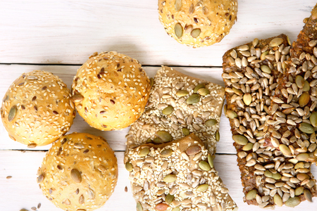 Bread buns with various seeds on white wooden table. Bread roll and breadsticks with sesame, pumpkin, sunflower, flax seeds, top view.