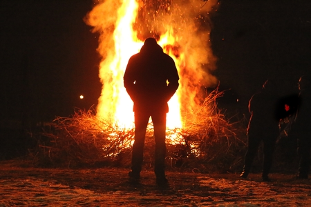 Silhouette of man by the fire at night. Man standing in front of bonfire. Flame on the ground. Фото со стока