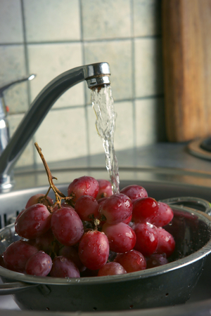 Washing fresh grapes in colander under the tap. Washing fruits in the kitchen sink. Stock Photo