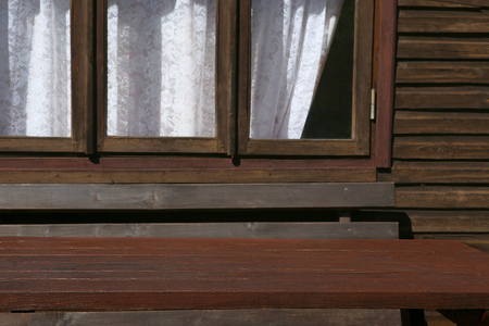 Wooden table in front of garden house with window. Empty table near summerhouse.