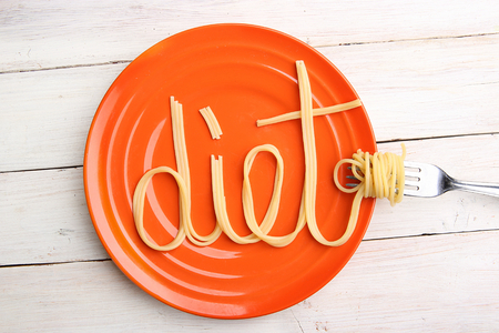 Word diet made from noodles in orange plate. Fun concept of dieting. Cooked spaghetti in plate and spaghetti swirls at fork.
