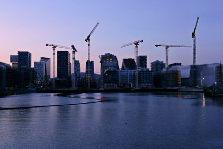 Background of silhouette skyscrapers and cranes under construction. Industrial city landscape at night, Bjorvika, Oslo, Norway. Stock Photo