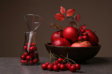 Autumn still life with hawthorn berries and apples. Composition of red berries and fruits in interior. Archivio Fotografico