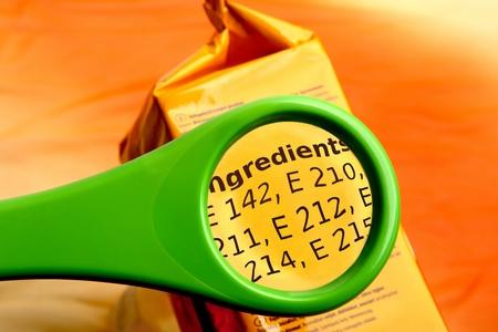Concetto di lettura degli ingredienti con lente d'ingrandimento. Lente d'ingrandimento sull'etichetta degli additivi alimentari. Archivio Fotografico