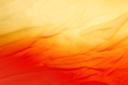 Abstract orange fabric background. Red and yellow blurred background.