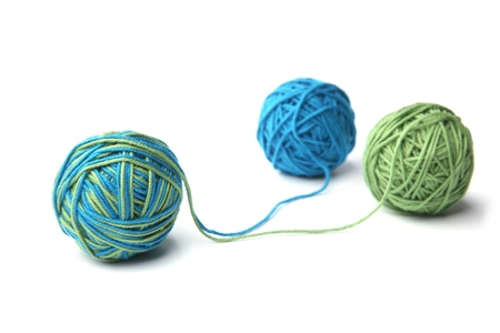 Colorful cotton thread balls isolated on white background. Different color green and blue thread mix.
