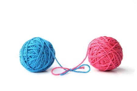 Two pink and blue cotton balls isolated on white background. Different color pink and blue thread balls.