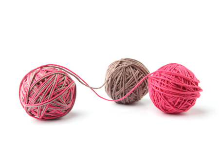 Colorful cotton thread balls from two color pink and grey thread isolated on white background. Different color pink and grey thread mix.