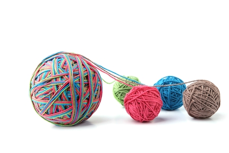 Colorful cotton thread ball from four color thread isolated on white background. Different color pink, green, grey, blue thread mix.