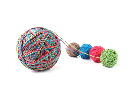 Sfera di filo di cotone colorato grande da filo di quattro colori isolato su priorità bassa bianca. Mix di fili di colore diverso rosa, verde, grigio, blu.