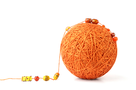 Orange big thread ball with jewelry beads isolated on white background. Ball of cotton string with glass beads.