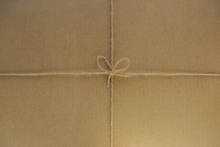 Tied string on cardboard background. Paper box tied with linen twine or rope.