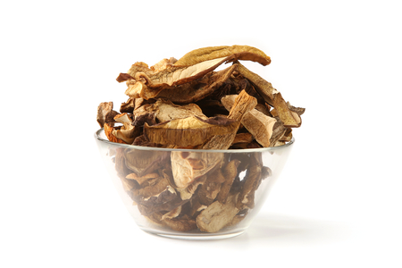Dried mushrooms in glass bowl isolated on white background. Wild edible dried boletus mushrooms.