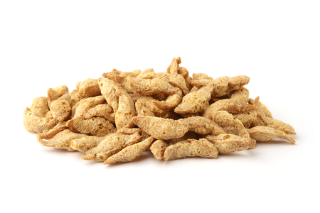 Raw soy chunks pile isolated on white background. Dry soya pieces meat used in vegetarian and vegan food.