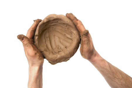 Pièce d'argile naturelle de modélisation dans les mains isolées sur fond blanc. Matériau d'argile humide pour la sculpture ou le modelage.