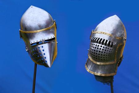 Medieval knight helmets on blue tent background. Iron helmets in the medieval knight tournament.