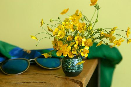 Wild yellow flowers, meadow buttercup, in small vase. Bouquet of fresh wild flowers, Ranunculus acris, indoor.