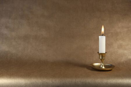 Burning candle in vintage metal candlestick on dark golden paper background with copy space.