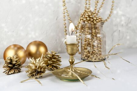 Golden Christmas decoration. Candle, balls, cones and garland indoor.