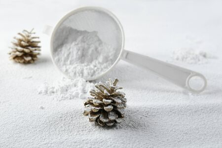 Christmas decoration cones covered snow made of icing sugar with sieve. Christmas forest concept. Golden colored pine cones covered sugar powder and sieve.