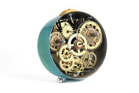 Back side of old mechanical table clock isolated on white background. Clockwork details, pinions and wheels. Standard-Bild