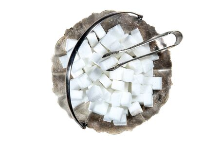 Sugar cubes in metal vintage sugar  bowl with sugar tongs isolated on white background top view.