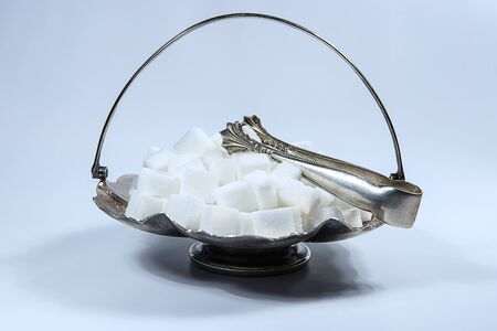 Sugar cubes in metal vintage sugar  bowl with sugar tongs.