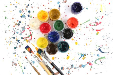 Jars with gouache paints and brushes on colorful paint splashes background. Plastic cans with multi-colored dye for drawing isolated on white background, top view.
