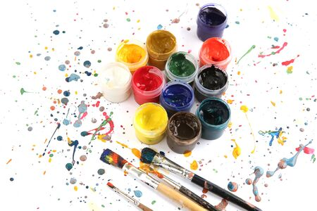 Jars with gouache paints and brushes on colorful paint splashes background. Plastic cans with multi-colored dye for drawing.