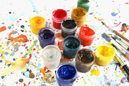Jars with gouache paints and brushes on colorful paint splashes background. Plastic cans with multi-colored dye for drawing. 版權商用圖片